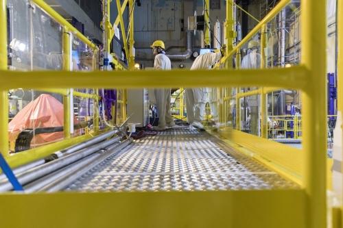 Opérateurs au travail sur une passerelle surplombant la piscine à la centrale nucléaire en démantèlement de Chooz A. | Philippe DUREUIL Photographie