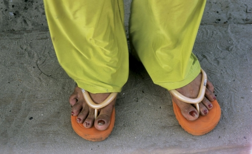 Pieds d'un homme aux ongles vernis en rouge portant des tongs orange et un pantalon vert fluo | Philippe DUREUIL Photographie