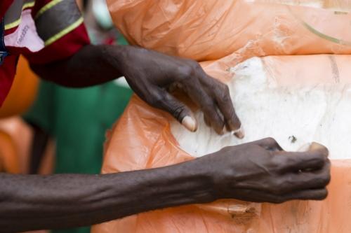 Photographique réalisée à Lomé pour le Groupe Necotrans. Un homme est au travail pour le contrôle qualité d'une Balle de coton. Agence de communication : Wellcom. | Philippe DUREUIL Photographie