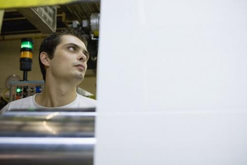 Jeunne homme au travail sur une ligne de production de tissus - Cliché réalisée pour le Groupe FERRARI TEXTILES | Philippe DUREUIL Photographie