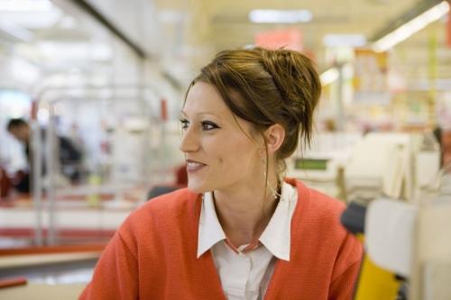 Photographie d'une hôtesse de caisse à son poste de travail réalisée pour le Groupe AUCHAN | Philippe DUREUIL Photographie