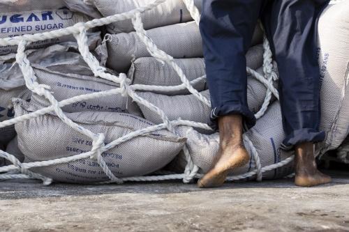 Photographique réalisée à Lomé, Togo, pour le Groupe Necotrans. Un homme est au travail pour décharger des sacs de sucre. Agence de communication : Wellcom. | Philippe DUREUIL Photographie
