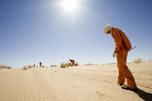 Photographie de reportage corporate réalisé pour Total Exploration Production dans le désert de Taoudéni en Mauritanie - Illustration d'une campagne de prospection sismique - Installation de géophones dans le sol | Philippe DUREUIL Photographie