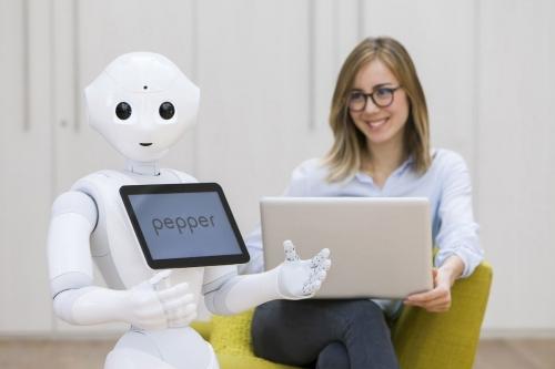 Woman at work confortablement assise sur son lieu de travail lumineux. Elle travaille avec le robot Pepper. Annonceur : SoftBank Robotics. Agence Toma. DA : Aurélien Esquivet. Décor : Treizeephemere. | Philippe DUREUIL Photographie