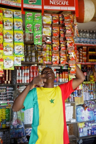 Vendeur dans sa boutique avec des produits Nescafé®. Reportage photo réalisé pour Nescafé®. | Philippe DUREUIL Photographie