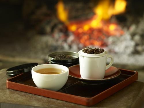Photo de nature morte d'un bol de thé présenté sur un plateau devant une cheminée. Photographie réalisée en studio pour l'enseigne Nature et Découvertes. Styliste culinaire : Garlone Bardel | Philippe DUREUIL Photographie
