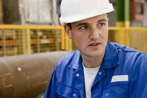Portrait d'un jeune ouvrier portant un casque dans une aciérie | Philippe DUREUIL Photographie
