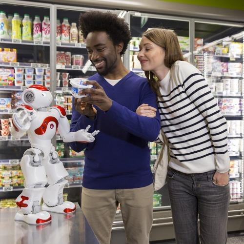 Un jeune couple souriant fait ses courses dans une supérette au rayon frais aidé par le robot Nao. Annonceur : SoftBank Robotics. Production photo : Agence Toma. DA : Aurélien Esquivet. | Philippe DUREUIL Photographie