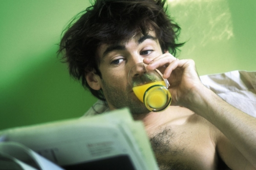 Homme au réveil dans sont lit qui boit un jus d'orange et lit le journal | Philippe DUREUIL Photographie
