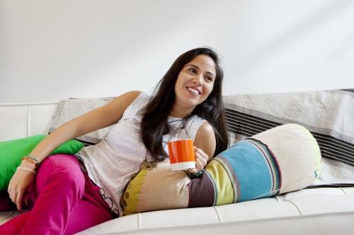 Photo lifestyle d'une jeunne femme souriante et détendue sur un canapé. Vie quotidienne à la maison. | Philippe DUREUIL Photographie