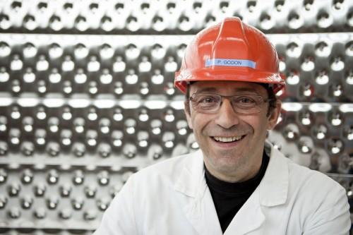 Photographie de portrait corporate d'un chercheur portant un casque de protection dans un cryostat géant. Reportage corporate réalisé au centre de recherche du CEA de Saclay. | Philippe DUREUIL Photographie