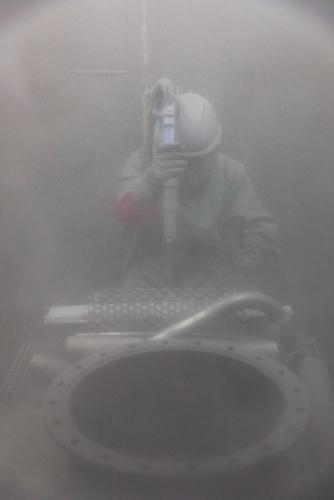Opérateur effectuant un grenaillage de pièces en acier pour décontamination à la centrale nucléaire en démantèlement de Greifswald. | Philippe DUREUIL Photographie