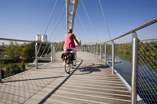 Femme en vélo sur une passerelle