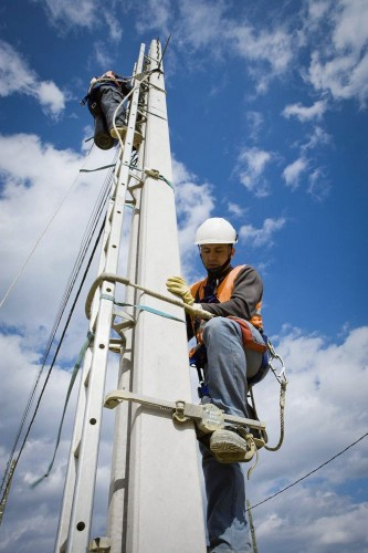 Photo industrielle d'hommes en formation sur un poteau béton de lignes électriques basse tension