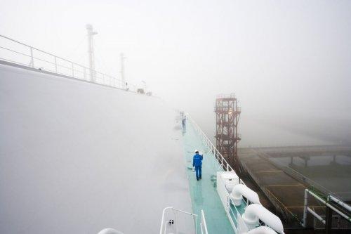 Photographie industrielle d'un méthanier à quai dans le brouillard