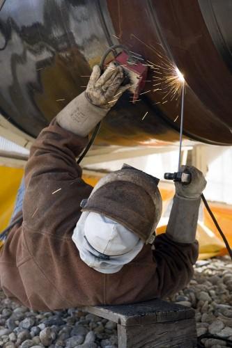 Photographie industrielle d'un soudeur au travail sous un gazoduc