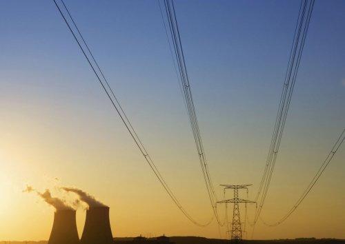 Photographie industrielle d'une centrale nucléaire au coucher de soleil