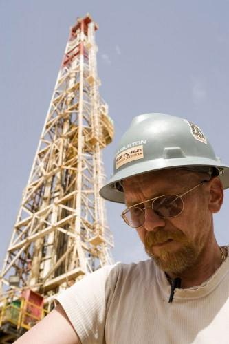 Photographie industrielle exploration gaz & pétrole Opérateur casqué devant un rig de forage