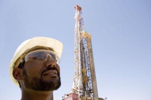 Photographie industrielle prospection gazière - Portrait d'un homme casqué devant un rig de forage
