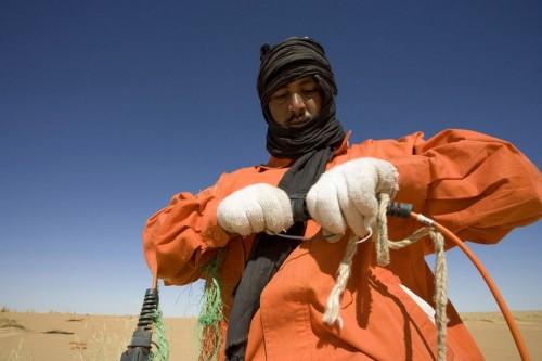 Photographie industrielle prospection sismique opérateur installant un géophone dans le désert