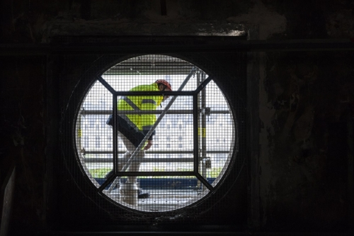 Homme équipé de ses EPI en train de se déplacer sur un échafaudage installé en extérieur | Philippe DUREUIL Photographie