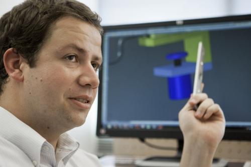 Portrait d'un ingénieur qui travaille sur la conception d'une pièce en 3D. Photo corporate d'un homme au travail réalisée pour Radian Éclairage. | Philippe DUREUIL Photographie
