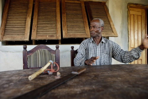 Portrait d'un fermier devant sa maison en Côte d'Ivoire. Sa machette et son lance pierre sont posés sur la table. | Philippe DUREUIL Photographie
