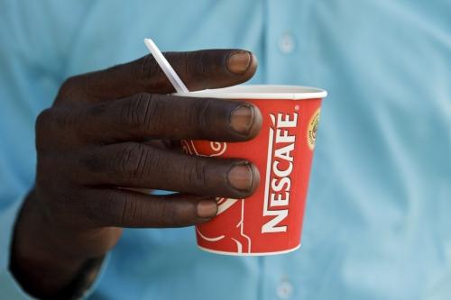 Homme tenant un gobelet de café Nescafé® à la main