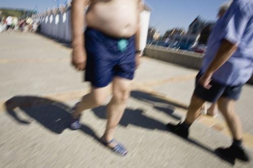 Homme qui se promène en maillot de bain avec un gros bide