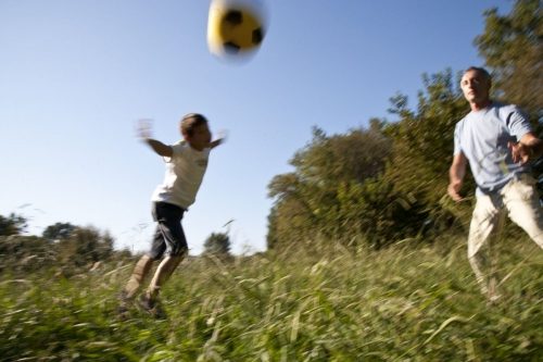 Enfant qui joue au ballon avec son père dans un parc | Philippe DUREUIL Photographie