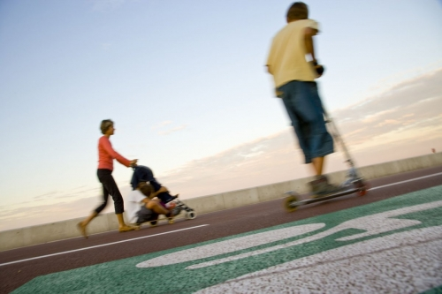 Enfant sur une patinette et mère de famille avec une poussette
