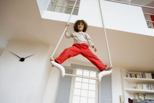Enfant sur un trapèze de cirque dans un appartement