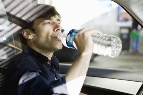 Photo d'un homme qui boit de l'eau au volant de sa voiture | Philippe DUREUIL Photographie