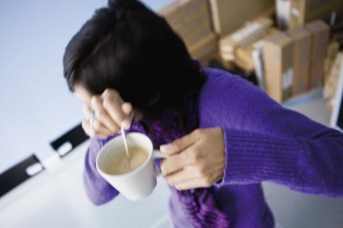 Femme qui se cache le visage au bureau avec son café | Philippe DUREUIL Photographie