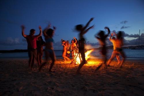 Photographie Lifestyle d'une fête autour d'un feu de camp. Agence Horizon Bleu. Annonceur : ODT de l' Île Saint-Martin. DA : Jérôme Dumas. | Philippe DUREUIL Photographie