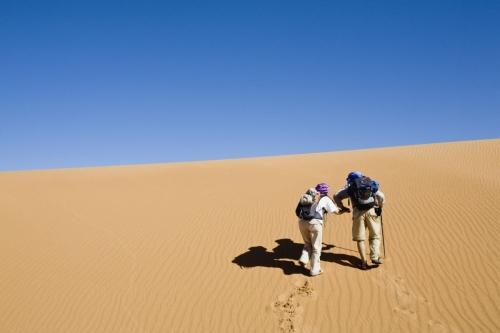 Couple de randonneurs qui monte sur une dune dans le désert | Philippe DUREUIL Photographie