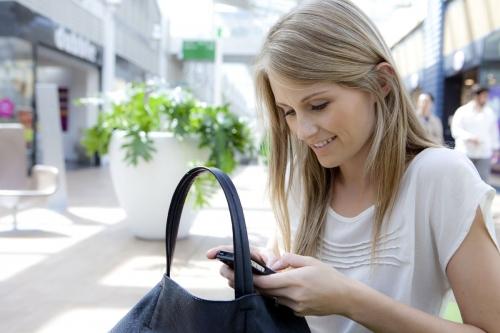 Reportage photo life-style dans un centre commercial - Portrait d'une femme assise qui consulte son smartphone. Production photo lifestyle : agence Objectif Images. | Philippe DUREUIL Photographie