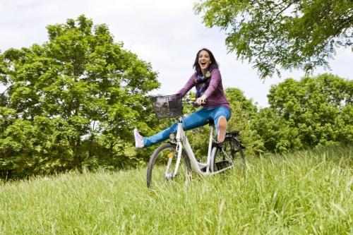 Femme qui fait du vélo sur l'herbe dans un parc de loisirs | Philippe DUREUIL Photographie